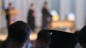 Ceremonia de graduación de observación de la gente en el pasillo de la universidad, acceso a la educación almacen de metraje de vídeo