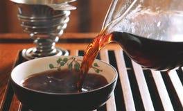 Ceremonia de té china con el té del puerh, cuenco caliente de relleno del té negro con té Imagenes de archivo