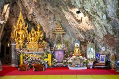 Ceremonial alms and kneeled monks inside Wat Tham Pha Plong Temple, Chiang Dao stock image