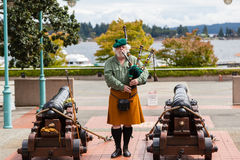 Ceremonial Bagpipe Performance at Nanaimo, BC. A Scottish bagpipe player performs prior to the daily cannon firing ceremony at the historic Bastion. The daily royalty free stock image