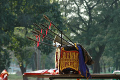 A Ceremonial Chair. A lushly decorated chair used by in ceremonies in Thailand. It is gold and draped in red and blue, with ceremonial spears. Behind are some royalty free stock images