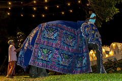 A ceremonial elephant has its colourful cloak  fitted prior to the Esala Perahera in Kandy, Sri Lanka. The Esala Perahera is held to honour the Sacred Tooth Royalty Free Stock Photography