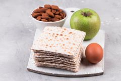 Ceremonial foods on the Passover holiday. Seder table ingredients: matzo bread, hard-boiled eggs for Beitzah, apple and nuts for Charoset. Happy Passover Stock Photos