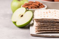 Ceremonial foods on the Passover holiday. Seder table ingredients: matzo bread, hard-boiled eggs for Beitzah, apple and nuts for Charoset. Happy Passover Royalty Free Stock Photo