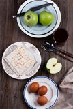 Ceremonial foods on the Passover holiday. Seder table ingredients: matzo bread, hard-boiled eggs for Beitzah, wine, apple and nuts for Charoset. Happy Passover Stock Photography