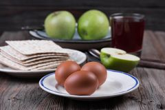 Ceremonial foods on the Passover holiday. Seder table ingredients: matzo bread, hard-boiled eggs for Beitzah, wine, apple and nuts for Charoset. Happy Passover Stock Photo