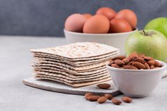 Ceremonial foods on the Passover holiday. Seder table ingredients: matzo bread, hard-boiled eggs for Beitzah, apple and nuts for Charoset. Happy Passover Royalty Free Stock Image