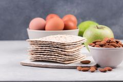 Ceremonial foods on the Passover holiday. Seder table ingredients: matzo bread, hard-boiled eggs for Beitzah, apple and nuts for Charoset. Happy Passover Stock Photo