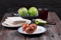 Ceremonial foods on the Passover holiday. Seder table ingredients: matzo bread, hard-boiled eggs for Beitzah, wine, apple and nuts for Charoset. Happy Passover Royalty Free Stock Image