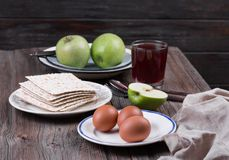Ceremonial foods on the Passover holiday. Seder table ingredients: matzo bread, hard-boiled eggs for Beitzah, wine, apple and nuts for Charoset. Happy Passover Royalty Free Stock Photo