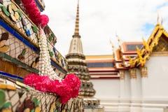Ceremoniella blommagarneringar runt om en pagod på Wat Pho Temple Royaltyfri Bild