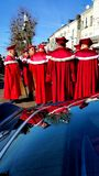 Company of French winetasters in red ceremonial dress. French  Company of brotherhood of Chinon wines in red ceremonial dress with robes reflected in vintage car Royalty Free Stock Photo