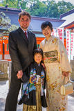 7-5-3 Ceremony Family Photo. An international couple, White and Japanese, pose with their child in suit and kimono in front of a shrine for a 7-5-3 Ceremony, a Royalty Free Stock Photography