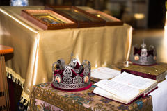 Ceremony of the wedding in the Russian Orthodox Church. The crowns lie near the bible close up stock photography