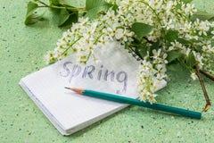 Cereza de pájaro y un cuaderno con las palabras: primavera fotos de archivo libres de regalías