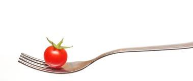 Cereza del tomate en una fork Imagen de archivo