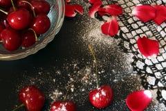 Cereza dulce contra el fondo negro, dibujo de encaje de la formación de hielo Foto de archivo