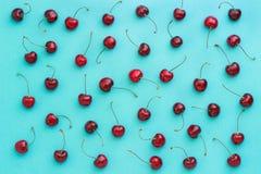 Cereza dulce madura roja en el fondo azul, textura Imagen de archivo libre de regalías