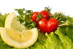 Cereza roja del tomate dos en el slidce verde de la ensalada y del limón del iceberg imagen de archivo