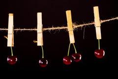 Cereza y cuerda en negro con la abrazadera Fotos de archivo libres de regalías