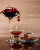 Cerezas, brandy y un pedazo de torta de chocolate Imagen de archivo libre de regalías