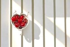Cerezas Chile en taza en forma de corazón en la madera Foto de archivo