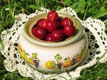Cerezas de las bayas en un pote de cerámica Fotos de archivo