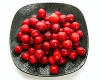 Cerezas dulces en plato negro Fotos de archivo libres de regalías