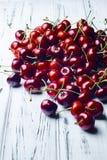 Cerezas dulces jugosas maduras en la tabla de madera blanca Imagen de archivo