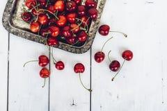 Cerezas dulces maduras en la bandeja de plata en la tabla de madera pintada Fotografía de archivo libre de regalías