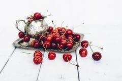 Cerezas dulces maduras en la bandeja de plata en la tabla de madera pintada Imágenes de archivo libres de regalías