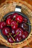 Cerezas dulces recientemente escogidas orgánicas maduras en taza del esmalte del vintage en cesta de mimbre Tabla del jardín Visi imágenes de archivo libres de regalías