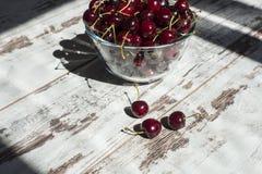 Cerezas dulces rojo oscuro en cuenco transparente Imagenes de archivo