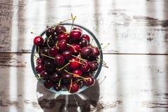 Cerezas dulces rojo oscuro en la opinión superior del cuenco transparente Fotografía de archivo