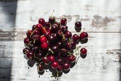 Cerezas dulces rojo oscuro que mienten en pila en la opinión de sobremesa de vintage-mirada Fotografía de archivo libre de regalías