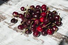 Cerezas dulces rojo oscuro que mienten en pila en vista lateral de vintage-mirada de la tabla Imagen de archivo libre de regalías