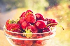 Cerezas dulces y fresas en una placa de cristal Fondo verde del vector con Bokeh D?a asoleado brillante Frutas jugosas, sabrosas fotografía de archivo libre de regalías