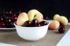 Cerezas dulces y melocotones del buñuelo Imagenes de archivo