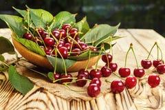Cerezas en cesta en la tabla de madera Cereza Cerezas en tazón de fuente Rojo Imágenes de archivo libres de regalías