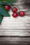 Cerezas en fondo de madera Foto de archivo libre de regalías