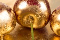 Cerezas en fondo del oro Fotos de archivo