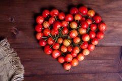 Cerezas en forma de corazón en la tabla de madera Imágenes de archivo libres de regalías