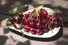 Cerezas en la placa blanca El día soleado, verano, salud natural come fotos de archivo