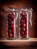 Cerezas en los tarros de cristal Fotografía de archivo libre de regalías
