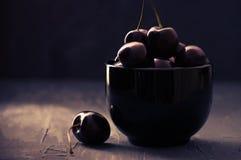 Cerezas en tazón de fuente negro Fotos de archivo