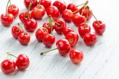 Cerezas en un fondo blanco Bayas rojas con las ramitas verdes Fotografía de archivo libre de regalías