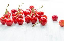 Cerezas en un fondo blanco Bayas rojas con las ramitas verdes Imagenes de archivo