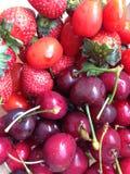 cerezas, fresas y tomates para el relevo del desayuno Imagen de archivo libre de regalías