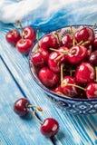 Cerezas frescas en un cuenco azul Foto de archivo libre de regalías