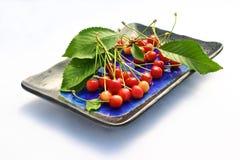 Cerezas frescas en una placa Imagen de archivo libre de regalías